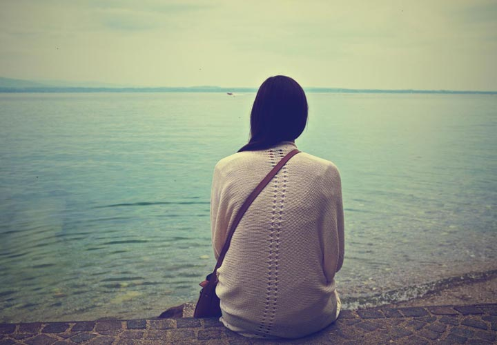 زنی که به تنهایی در ساحل نشسته است