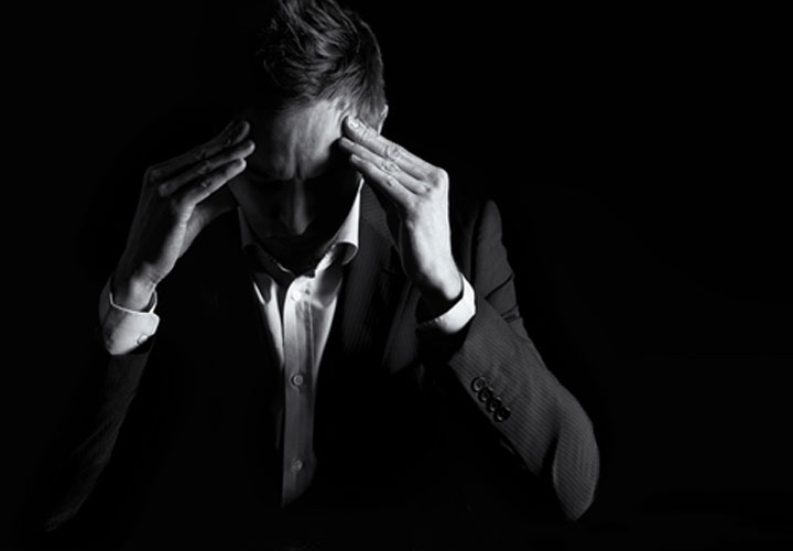تصویر مردی که با پریشانی دست بر پیشانی دارد