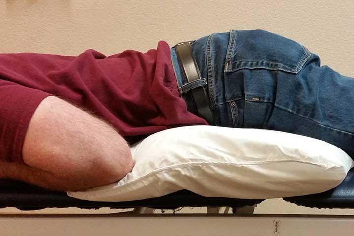 روی شکم بخوابید و بالشی زیر شکمتان قرار دهید