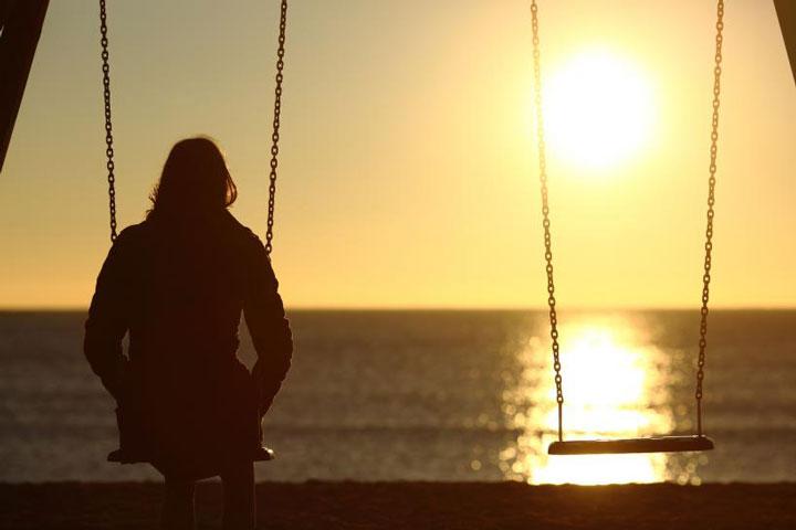 دختری تنها روی تاب در کنار ساحل